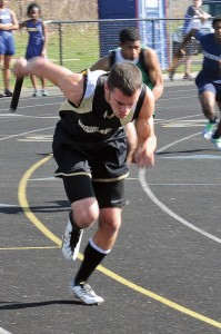 Woodland's Mike Lang gets things started for the Hawks' 4-by-100 relay squad during a meet Tuesday in Beacon Falls. Lang, a junior, is no stranger to sprinting, but he has made a name for himself in the jumping events. –LUKE MARSHALL