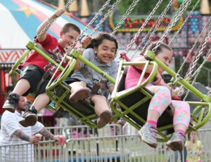 Children enjoy a ride on the swings during the St. Francis-St. Hedwig School Home School Association's carnival last year on the St. Francis Field on Church Street in Naugatuck. –FILE PHOTO