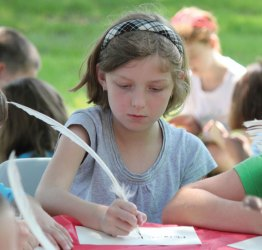Algonquin School third-grader Morgan Marchant tries her hand at writing with a quill pen on the Town Green May 30. Third-graders from the school in Prospect stepped back in time to learn about the town and its history. The students toured Town Hall, Prospect Cemetery, the Center One schoolhouse and the Hotchkiss House and barn. As part of the day, students wrote with quill pens and played games from yesteryear. The program was organized by third-grade teachers Marcia Beltrami, Elena Guerra and Kathleen Bicio and the Prospect Historical Society. The program was funded through the Region 16 innovative grant initiative. The program ties into the state's social studies standards and the students will be creating a history book about Prospect for children. –ELIO GUGLIOTTI