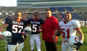 Former Woodland football players Jeremy Clark (57), Rahmi Rountree (5) and Eric Collodel (51) pose for a picture with Woodland football coach Tim Shea after the CHSCA Hall of Fame Classic Military Bowl June 29 at Rentschler Field in East Hartford. –KYLE BRENNAN
