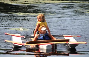 Joyce Krenesky, in front, and her granddaughter Micaela Guerra, both of Beacon Falls, pilot their cardboard boat back to shore July 6 on Carrington Pond at Matthies Park during Beacon Falls' first Cardboard Boat Regatta. –FILE PHOTO