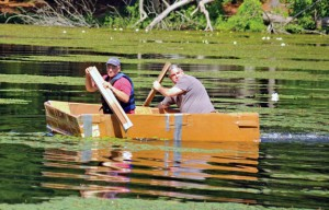 Beacon Falls Parks and Recreation Commission Chairman Joe Rodorigo, right, and commission member Domenick Sorrentino paddle their cardboard boat July 6 on Carrington Pond at Matthies Park during Beacon Falls' first Cardboard Boat Regatta. Their boat sank as the two men were paddling back to shore. –LUKE MARSHALL