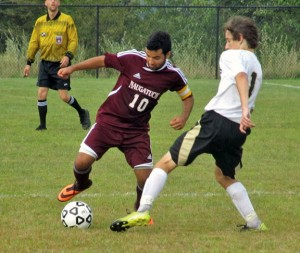 Naugatuck's Ygor Silva (10) works to dribble past Woodland's Thomas Bethin (1) Sept. 12 in Beacon Falls. The Greyhounds won the game, 7-0. –KYLE BRENNAN