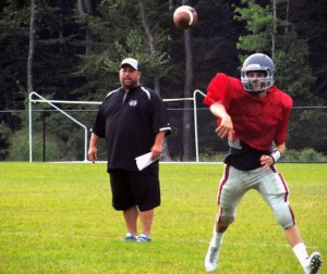 Naugatuck junior quarterback Jason Bradley throws a pass in a 7-on-7 drill against Oxford late last month as first-year head coach Craig Bruno looks on. The Greyhounds open the season Sept. 13 at Crosby. –KYLE BRENNAN