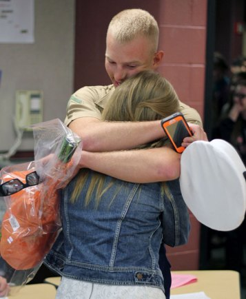 U.S. Marine James Tompkins, 19, of Prospect, hugs his sister, Lauren, 17, at Woodland Regional High School in Beacon Falls Sept. 26. James Tompkins, who recently completed military occupancy school and will be deployed to Afghanistan in December, surprised his sister during the last period of the day. –ELIO GUGLIOTTI