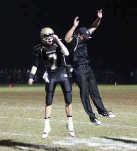 Woodland quarterback Tanner Kingsley (7) and assistant coach Jake Pinho celebrate after a touchdown Oct. 4 against Naugatuck in Beacon Falls. The Hawks won the Copper Division showdown, 25-22. –ELIO GUGLIOTTI