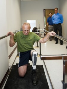 Craig Gambacini, of Naugatuck, demonstrates how he can kneel using a motorized prosthetic leg at New England Orthotics and Prosthetics in Middlebury Nov. 6. Looking on is Ian Duggan and Brad Scott, with Ossur. –RA ARCHIVE