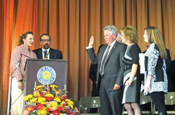 Prospect Mayor Robert Chatfield, center, stands with his wife, Ginny and his daughter, Leslie as he is sworn in for his 19th term by, at left, state Rep. Lezlye Zupkus (R-89) and retired Community School Principal Joseph Nuzzo Nov. 15 at Community School. –LUKE MARSHALL Naugatuck Mayor Robert Mezzo, left, is sworn in by Judge of Probate Peter Mariano at City Hill Middle School Nov. 19. Mezzo won his third term in office on Nov. 5. –LUKE MARSHALL
