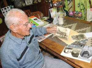 World War II veteran Martin Litschauer, 93, looks over photos from his time in the service Nov. 1 at Terri's Flower Shop in Naugatuck, which is owned by his daughter, Lydia LeBlanc. –LUKE MARSHALL