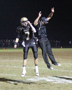 Woodland quarterback Tanner Kingsley (7) and assistant coach Jake Pinho celebrate after a touchdown Oct. 4 against Naugatuck in Beacon Falls. The Hawks topped the Greyhounds to win the first George Pinho Memorial Trophy. –ELIO GUGLIOTTI