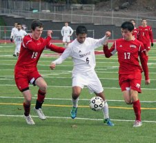 Naugatuck's Diogo Cruz (6) battles with Masuk's Nicholas Zacchilli (19) and Zachary Schulz (17) to keep control of the ball Nov. 7 during the second round of the Class L tournament in Naugatuck. The Greyhounds won the game, 2-0, but fell in overtime to Farmington Nov. 9 in the quarterfinals. –ELIO GUGLIOTTI