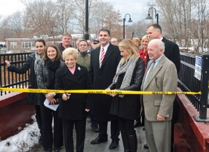 "Naugatuck resident Mary Louise Mallane, center, cuts the 'ribbon' to officially open the first section of the Naugatuck pedestrian greenway while local and state dignitaries look on Dec. 20. That section of the greenway was dedicated to Mallane's late husband ""Irish"" Patrick Mallane, Sr., a lightweight boxer who lived in the Union City section of Naugatuck. –LUKE MARSHALL"