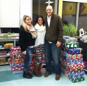Naugatuck High students Michelle Wright, left, and Shawnna Garcia pose for a picture with Calvary Chapel Church Pastor Jered Murphy in front of presents at Naugatuck Head Start in Central Avenue School. The presents were for Operation Head Start, a program initiated by the church for third year in a row for the holidays. Students and staff from Naugatuck High helped out with the program as well. Wright and Garcia coordinated, supervised and dropped off of all of the boxes.-CONTRIBUTED