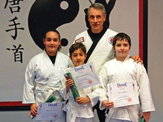 Naugatuck YMCA youth karate students, front row from left, Rebecca Santos, David Fernandes and Paul Melo received their green belt 6 on Dec. 12. They were graded by Grand Master Robert Cheezic at USA Martial Arts in Naugatuck. The students were graded on the discipline and skills they learned, demonstrated four forms and spared other students. Their instructor, 7 degree master belt Joe Antonucci (pictured with the students) also provided over the grading. Karate classes at the YMCA are held Mondays from 4:30 to 5:30 p.m. and will begin again in January. For more information, contact the YMCA at (203) 729-9622 or naugatuckymca@yahoo.com. –CONTRIBUTED