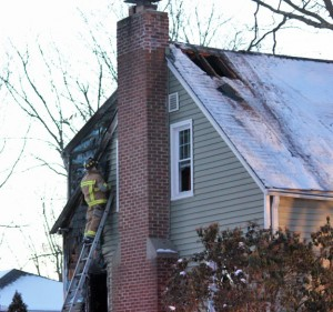 A Naugatuck firefighter works at he scene of a house fire at 100 Conrad St. in Naugatuck Wednesday afternoon. –ELIO GUGLIOTTI
