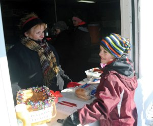Alex Kuczenski, 10, of Naugatuck talks with Park Commission member Linda Ramos Saturday at the snack hut near the portable ice skating rink on the St. Francis Church Field in Naugatuck. The rink officially opened for the first time Saturday. –LUKE MARSHALL