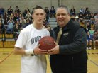 Woodland senior guard Tanner Kingsley, left, is presented a game ball from Woodland boys basketball coach Tom Hunt Jan. 11 for becoming the first player in the history of the boys basketball program to reach 1,000 points. Kinglsey, who was honored before the Hawks game versus Naugatuck in Beacon Falls, reached the milestone Jan. 7 with 24 points against Holy Cross. –KYLE BRENNAN