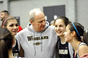 Woodland relay runners, from left, Ava Capuano, Val Vinca and Erin Machado celebrate with girls indoor track coach Jeff Lownes after winning the 4-by-800-meter relay Jan. 28 at the NVL indoor boys and girls track championships at the Floyd Little Athletic Center at Hillhouse High School in New Haven. Clara Drozdowski, not pictured, was the fourth runner in the relay. –FILE PHOTO