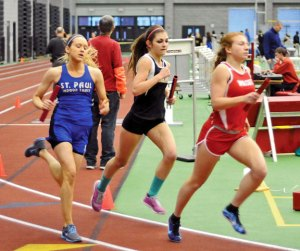 Woodland's Ava Capuano, center, fights for position against runners from St. Paul and Wolcott Jan. 28 during the 4-by-800-meter relay at the NVL indoor boys and girls track championships at the Floyd Little Athletic Center at Hillhouse High School in New Haven. The Hawks team of Capuano, Val Vinca, Erin Machado and Clara Drozdowski won the event, and the girls team took home the title. -LUKE MARSHALL