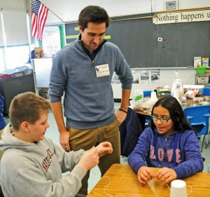 University of Connecticut student Josh Leveillee looks on as Cross Street Intermediate School fifth-graders William Brown, left, and Gabriella Jordan create a machine out of string, paperclips and rubber bands that will help them stack cups Feb. 4. –LUKE MARSHALL