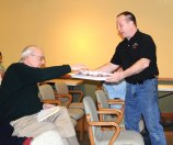Robert Prifty of Naugatuck takes a sample of beer from Mark Szamatulski during a craft beer making and tasting event at the Whittemore Library in Naugatuck March 5. Mark and Tess Szamatulski, who own Maltose Express, a home brewing and wine making supply store in Monroe, came to the library to give a class on making beer. –LUKE MARSHALL