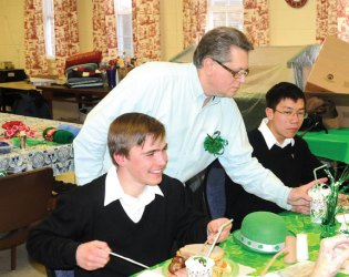 Naugatuck Senior Center Director Harvey Frydman serves a cup chocolate to Paul Yip of the Legion of Christ College in Cheshire as Paul Lasota looks on during the senior center's St. Patrick's Day March 6. Yip and Lasota, along with about a dozen other members of the seminary, were at the senior center as part of the seminary's Novitiate Choir to sing traditional Irish songs for the seniors. –LUKE MARSHALL