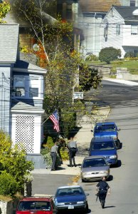 Police approach 84 High St. in Naugatuck in 2006. Ryan Ramey, a Naugatuck man, barricaded himself inside the home and was convicted of lighting it on fire. –RA ARCHIVE