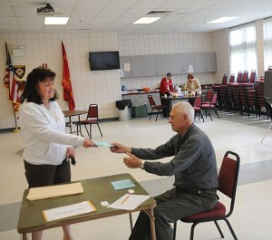 Marlene Wentworth of Prospect receives a ballot from Roland Brunetti to vote in the Region 16 budget referendum Tuesday at the Prospect firehouse. The $39.7 million 2014-15 budget for the district, which oversees schools in Beacon Falls and Prospect, was approved 493 to 441. –LUKE MARSHALL