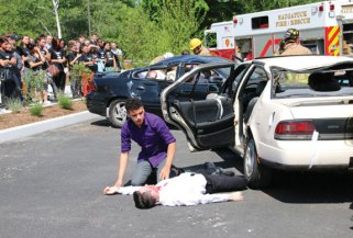 Naugatuck High School senior Preston Bogan checks on the condition of senior Jason Begin during a mock crash at the high school May 30. The high school's prom was later that evening and the mock crash was put on with the help of Naugatuck Ambulance, as well as the Naugatuck fire and police departments to show the students what could happen if they drink and drive. –LUKE MARSHALL