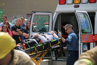Naugatuck High School senior Jason Begin is loaded into an ambulance by Dave Begey, an EMT with Naugatuck Ambulance, during a mock crash at the high school on May 30. The high school's prom was later that evening and the mock crash was put on with the help of Naugatuck Ambulance, as well as the Naugatuck fire and police departments to show the students what could happen if they drink and drive. –LUKE MARSHALL