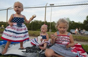 Sisters Madalynn and Abagail Warzecha, both 19 months, and Maci Warzecha, 3, enjoy ice cream while waiting for the fireworks to begin during the Naugatuck's annual Fourth of July Celebration Sunday in Naugatuck. –RA ARCHIVE
