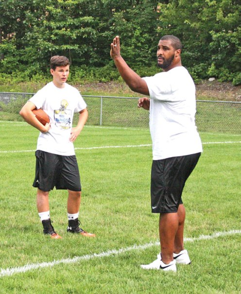 Former NFL quarterback Daunte Culpepper gives advice to Nick Cilfone of Watertown during the Bags All-Star Football Camp hosted by the Woodland Jr. Hawks July 19 at Caplan Park in Prospect. Culpepper, who played 11 seasons in the NFL, worked with campers on proper stances and on how to throw a pass. –LUKE MARSHALL