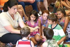 Rae Griffiths, owner and principal educator of the Belchertown, Mass.-based Teaching Creatures, shows a bearded dragon to children at the Prospect Public Library Tuesday afternoon. Griffiths visited the library as part of the summer events program. In addition to the bearded dragon, Griffiths also introduced the children to an ornate wood turtle and a corn snake. –LUKE MARSHALL