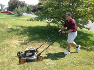 Naugatuck Mayor Robert Mezzo mows the lawn of a resident Kerry McLaughin on Meadow Lark Drive in the borough Wednesday to help the resident raise money for charity. –RA ARCHIVE