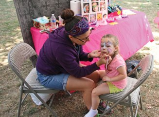 Madison Schomburg, 3, of Seymour has her face painted by Jennifer Pappas Aug. 23 during the All Arts Festival on the Naugatuck Green. –LUKE MARSHALL
