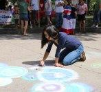Saleena Na of Naugatuck uses chalk to create a colorful design to welcome visitors Aug. 23 to the All Arts Festival on the Naugatuck Green. –LUKE MARSHALL