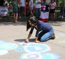 Saleena Na of Naugatuck uses chalk to create a colorful design to welcome visitors Aug. 23 to the All Arts Festival on the Naugatuck Green. –LUKE MARSHALL