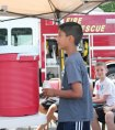 Sahil Banerjee, 9, of Beacon Falls delivers a glass of lemonade during the United Day School's lemonade stand July 24 along Main Street in Beacon Falls. For the past four years, children in the school's summer program have sold lemonade to benefit an organization in town. This year the money raised will go the Beacon Falls Senior Center. –ELIO GUGLIOTTI