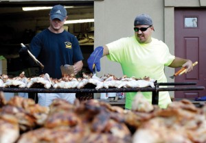 Tim Platt, left, of Bethlehem and John DeCampos Jr. of Naugatuck cook up chickens at the Sao Paio Feast at the Portuguese Club in Naugatuck in 2014. This year's festival is Labor Day weekend. -RA ARCHIVE