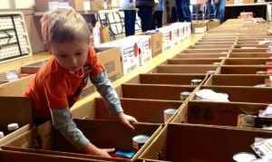 Connor Walker, 7, of Naugatuck, helps fill boxes with Thanksgiving Day meals for the Naugatuck Ecumenical Food Bank at St. Michael's Episcopal Church on the Town Green Sunday afternoon. A total of 285 boxes were filled Sunday. -REPUBLICAN-AMERICAN