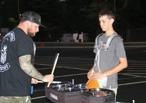 Naugatuck High School marching band percussion instructor Matt Richter, left, demonstrates proper technique to senior Tyler Wanciak during practice Sept. 24 at the high school. The band was practicing for the upcoming Thunder in the Valley competition, which will take place at 6 p.m. Oct. 3 at the high school. –LUKE MARSHALL