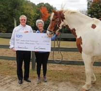 Ion Insurance President and CEO David Drescher presents a check for $415 to Hidden Acres Therapeutic Riding Center Program Director Jeanna Pellino. The money was raised through Ion Insurance's Quotes for a Cause program. –CONTRIBUTED