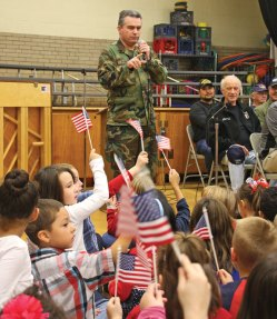 Retired U.S. Army Staff Sgt. Matthew Toms tells students at Western Elementary School in Naugatuck about the significance of the American flag Nov. 10 as students wave their flags. Toms was one of about two dozen veterans who visited the school to commemorate Veterans Day. –LUKE MARSHALL