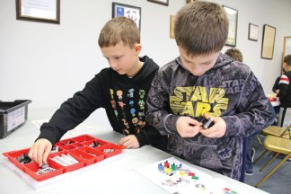 Fourth-grader Carter Davis, left, looks for the next Lego piece of a robot while his partner, fourth-grader Matthew Smith, works on attaching the proper parts to the robot Jan. 14 at Beacon Falls Town Hall as part of the Beacon Falls Library's Lego Robotics program. –LUKE MARSHALL