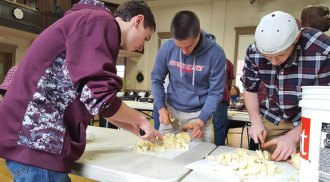 Members of the Naugatuck High School basketball team, from left, Corey Plasky, Tyler Deitelbaum and Shane Swierbitowicz peel and chop potatoes Christmas Eve morning at St. Michael's Church in Naugatuck in preparation for the Joy of Christmas Dinner. The annual dinner, which was served on Christmas, is hosted by a committee of volunteers and open to anyone who wanted to share a meal on the holiday. –LUKE MARSHALL