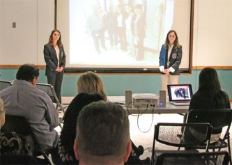 """Naugatuck High School DECA officers Amanda Rinaldi, left, and Alanna Readel present information on the issue of veteran homelessness to an audience at the Whittemore Library in Naugatuck Jan. 27. The presentation was part of a public relations project Rinaldi and Readel are working on for the state DECA competition. Rinaldi and Readel are also selling """"House A Vet"""" bracelets in conjunction with the Naugatuck Exchange Club. The bracelets are $5 each and all proceeds are going to a program dedicated to housing homeless veterans. To help veterans with a donation or for more information, contact DECA advisor Tim Reilly at reillyt@naugy.net or (203) 232-0725. –LUKE MARSHALL"""