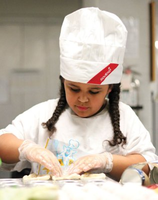 Andrew Avenue Elementary School fourth-grader Allie Palermo presses biscuit dough into a cupcake tin for her cheesy ham and egg biscuit cups during the Sodexo Future Chef competition March 9 at Naugatuck High School.–ELIO GUGLIOTTI