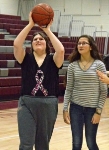 Naugatuck High School senior Kim SanAngelo, left, takes a shot with fellow student Jackie Aronin offering support during a recent Unified basketball practice at the school. –KEN MORSE