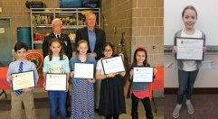 The Naugatuck Fire Department honored the winners of Naugatuck's 10th annual Connecticut Fire Prevention Poster Contest at fire headquarters March 16. Pictured, front row from left, winners Zach McCasland, Josephine Burke, Delilah Powell, Mireya Trelles, and Sophia Onofrio; back row from left, acting Deputy Fire Marshall William Scanlon and Naugatuck Mayor N. Warren 'Pete' Hess. Danille Johnson, pictured at right, was also among the winners. McCasland also won the New Haven County contest. –CONTRIBUTED