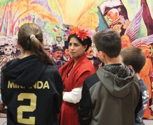 Long River Middle School Spanish teacher Stacey Groshart, dressed as the Mexican painter Frida Kahlo, discusses Diego Rivera's mural, 'Dream of a Sunday Afternoon in Alameda Park,' with students April 4 at the school. Long River and the world language department received a grant to rent the Teacher's Discovery Traveling Exhibit for two weeks. The exhibit features three life-sized reproductions of murals created by Rivera, a renowned Mexican artist. The exhibit was displayed at Long River for a week and will be displayed at Woodland Regional High School for a week. Woodland will host a student and parent viewing and reception at 6:15 p.m. on April 14 prior to the World Language Honor Society induction. –ELIO GUGLIOTTI